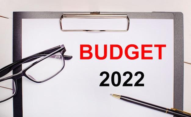 Su uno sfondo di legno chiaro occhiali, una penna e un foglio di carta con il testo budget 2022. concetto di business