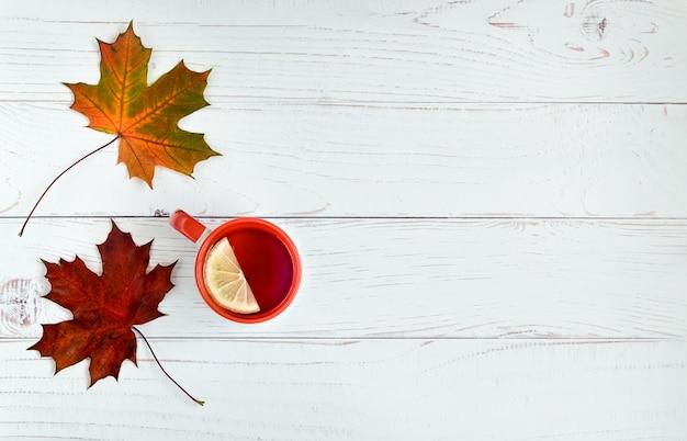 Fondo in legno chiaro con foglie d'autunno di acero e tazza di tè al limone