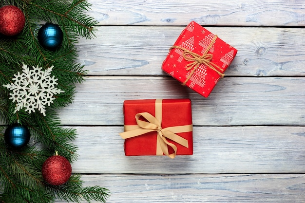 Sfondo in legno chiaro con regali di capodanno e rami di abete e un fiocco di neve con decorazioni natalizie