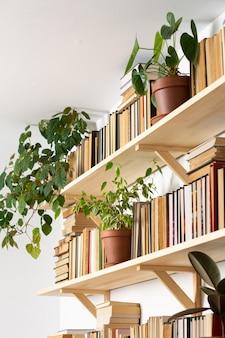 Scaffali in legno chiaro con libri rovesciati con copertina rigida in interni bianchi, fiori interni sugli scaffali, biblioteca domestica, design biofilo e piante