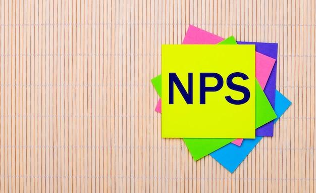 Su una superficie di legno chiaro, adesivi multicolori luminosi con il testo nps net promoter score