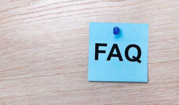 Su una superficie di legno chiara - un adesivo quadrato azzurro con il testo faq