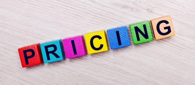 Su una superficie di legno chiara su cubi di legno luminosi multicolori la parola pricing