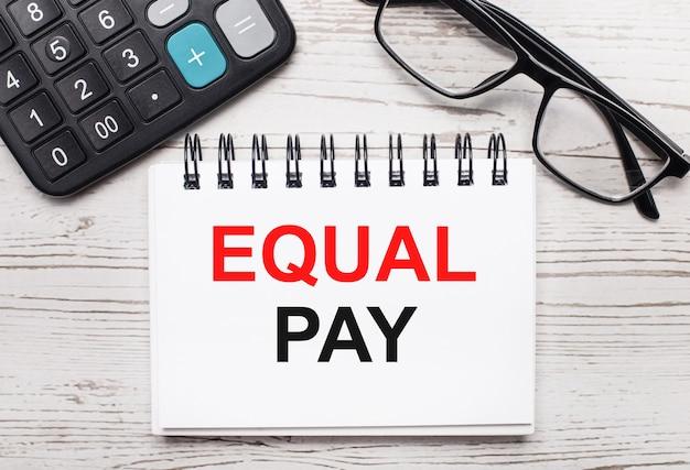 Su una calcolatrice da tavolo in legno chiaro, occhiali e un blocco note vuoto con il testo equal pay. concetto di affari