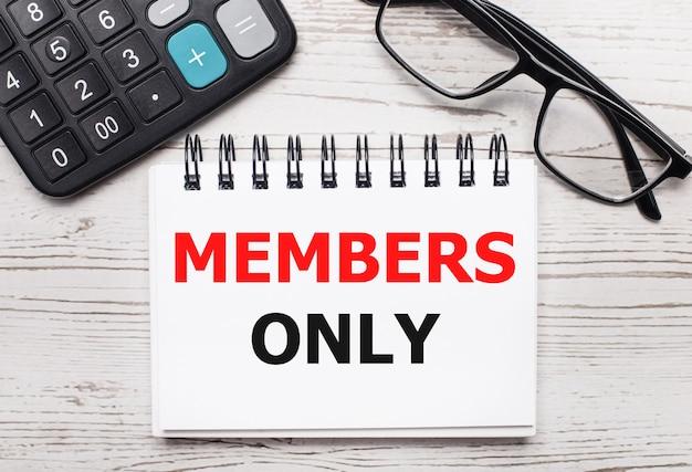 Su un tavolo di legno chiaro una calcolatrice, occhiali e un blocco note vuoto con il testo solo per i membri. concetto di affari