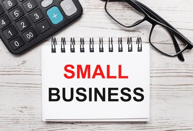 Su una calcolatrice da tavolo in legno chiaro, occhiali e un blocco note vuoto con il testo small business. concetto di affari