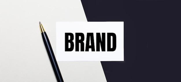 Su un tavolo di legno chiaro si trovano una calcolatrice, graffette multicolori e un taccuino con una penna e la parola brand