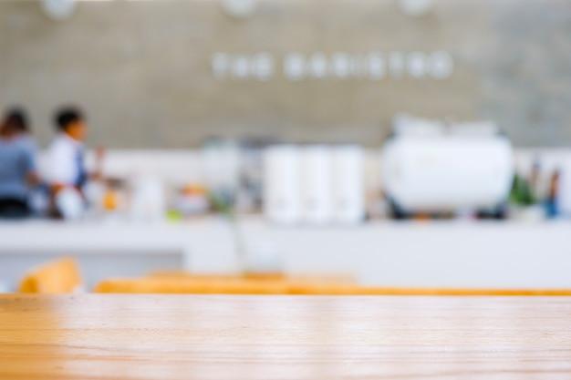 Tavolo in legno chiaro davanti a sfondo sfocato caffetteria o caffetteria