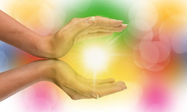 La luce nelle mani della giovane donna a forma di coppa. concetti di condivisione, dare, offrire, prendersi cura,