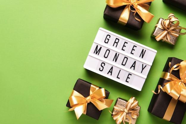 Lightbox con testo green monday sale su sfondo di carta verde con scatole regalo nere e fiocco dorato, copia spazio.