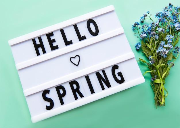 Lightbox con testo hello spring e bouquet di fiori non ti scordar di me su un tavolo verde
