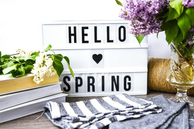 Lightbox con testo ciao primavera e bouquet di fiori lilla viola in vaso di vetro