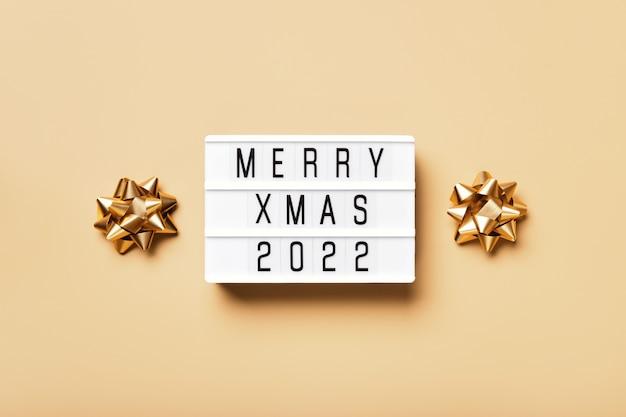 Lightbox con testo merry xmas 2022 e decorazioni natalizie dorate su sfondo beige. layout creativo in colori monocromatici neutri.