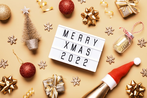 Lightbox con testo merry xmas 2022 e decorazioni natalizie dorate su sfondo beige. layout creativo in colori monocromatici neutri