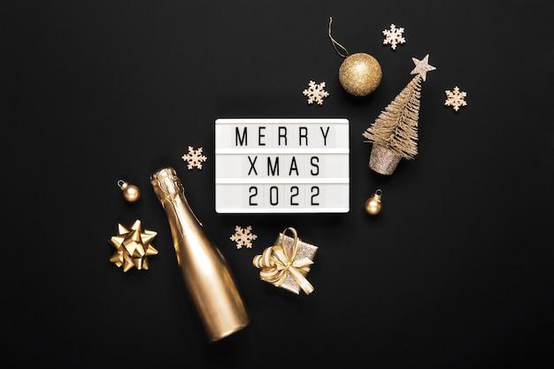 Lightbox con testo merry xmas 2022 e decorazioni natalizie dorate su sfondo nero. layout creativo in colori monocromatici.