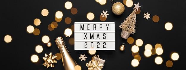 Lightbox con testo merry xmas 2022 e decorazioni natalizie dorate su sfondo nero. layout creativo in colori monocromatici