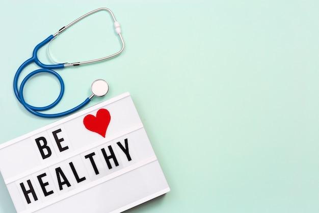 Lightbox con parole be healthy e stetoscopio blu su sfondo color menta