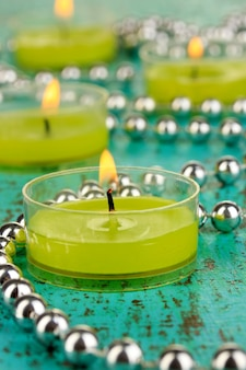 Candele accese con perline su sfondo verde