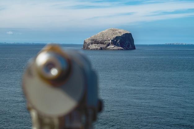Faro su una scogliera e c'è un telescopio sfocato in primo piano. bass rock, scozia, regno unito