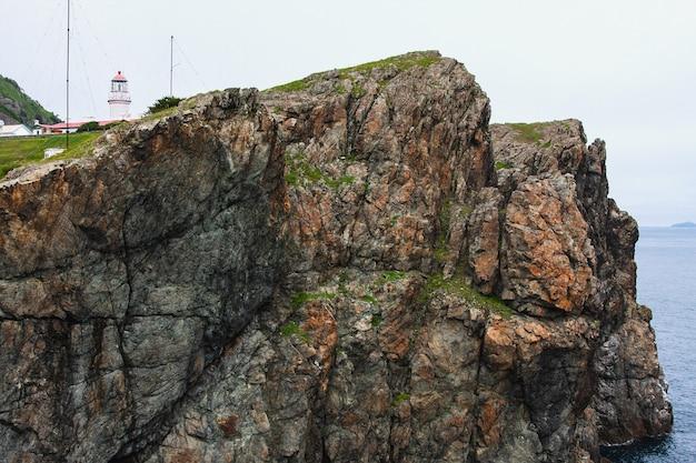 Faro, enormi rocce sull'oceano, paesaggio estivo marino, vecchio edificio in pietra su un'alta scogliera