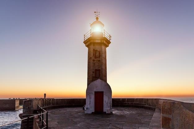 Faro sul tramonto sull'oceano