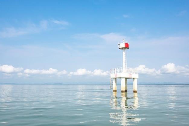Il faro nel mare con eflection di acqua sfondo nuvola e cielo.
