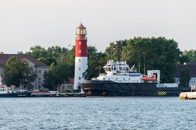 Faro nel porto marittimo. bellissimo faro russo baltiysk. cielo blu pulito.