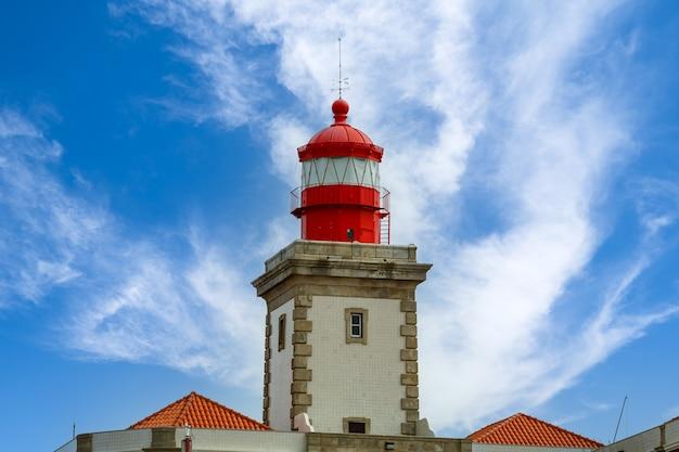 Faro in cima a una scogliera di roccia e cielo blu con nuvole. lisbona portogallo.