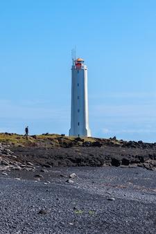 Faro sulla costa occidentale dell'islanda a tempo soleggiato. colpo verticale