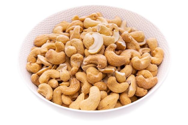 Anacardi leggermente arrostiti in una ciotola bianca prodotti alimentari closeupisolati