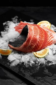 Trota leggermente salata. filetto di pesce fresco con ingredienti culinari, erbe aromatiche e limone su sfondo nero, vista laterale.