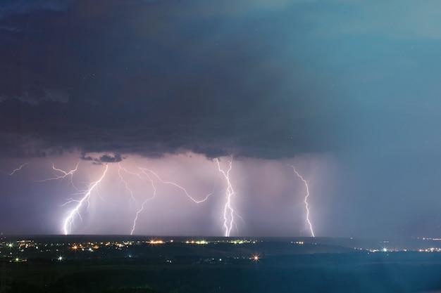 Tempesta di fulmini sulla città. colpo di fulmine nel cielo blu scuro nella città di notte.
