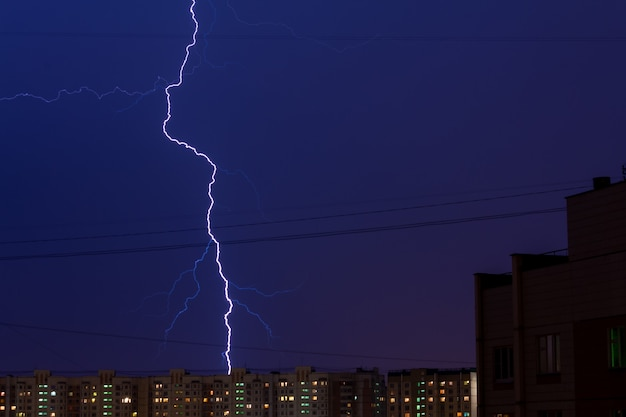 Colpo di fulmine nella città di mosca, russia. un fulmine in città di sera su edifici residenziali. cielo blu scuro.