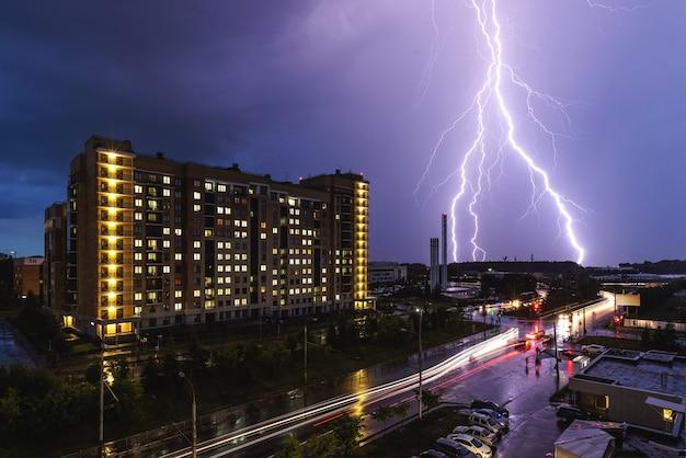 Un fulmine durante un temporale sullo sfondo di un edificio cittadino. traffico cittadino notturno.