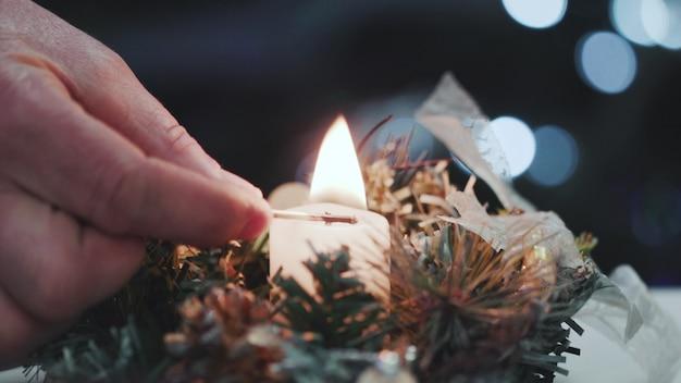 Accende le candele al tavolo di natale. primo piano della mano di un uomo che accende una candela