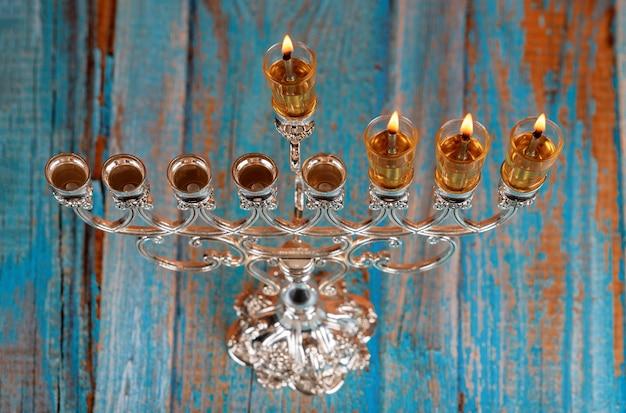 Accende le candele il terzo giorno della festa ebraica di hanukkah. le candele stanno bruciando la luce della menorah