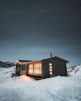 Luci da una capanna di legno nella remota natura selvaggia della groenlandia