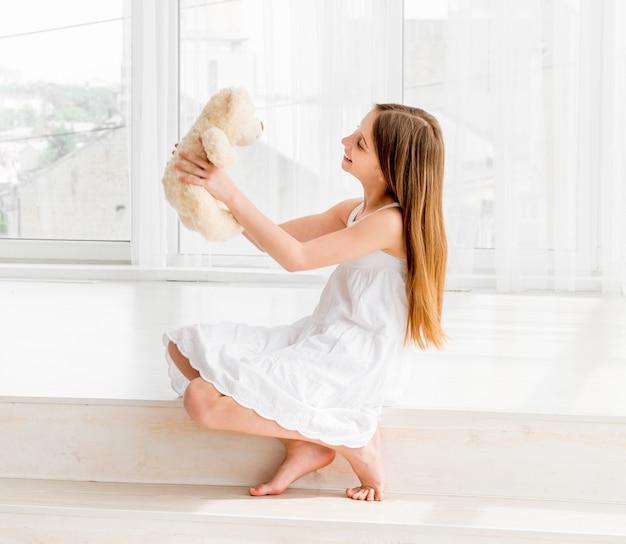 Liittle ragazza seduta sul pavimento e in possesso di orsacchiotto giocattolo