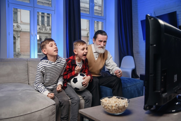 Simpatico nonno anziano con la barba concentrato con i suoi allegri nipoti di 10-15 anni che trascorrono il loro tempo libero a rivedere il gioco di basket in tv