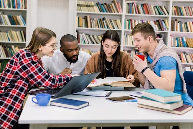 Amici di studenti multirazziali allegri eccitabili simpatici seduti al tavolo nella biblioteca universitaria, usando il computer portatile e leggendo libri