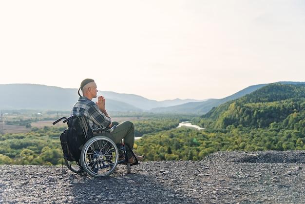 Simpatico giovane ragazzo incapace seduto da solo in sedia a rotelle sulla collina sulla splendida natura