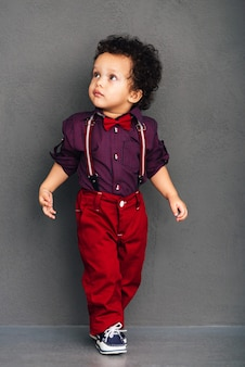 Come in passerella. piccolo neonato africano che guarda lontano mentre cammina su sfondo grigio