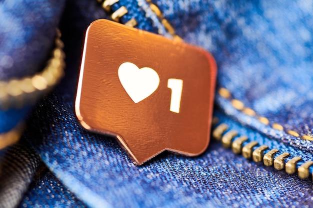 Come il simbolo del cuore. pulsante come segno, simbolo con cuore e una cifra. marketing di rete sui social media. fondo di struttura dei jeans blu.