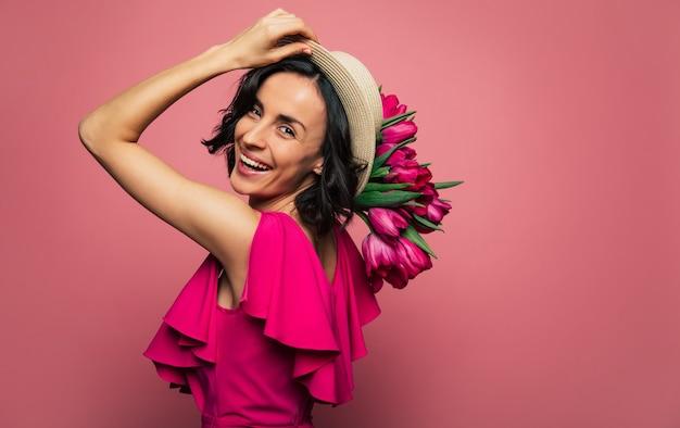 Come a parigi. una donna bruna con un cappello di paglia sta guardando nella telecamera sopra la sua spalla, mentre tiene un mazzo di tulipani nella mano destra.