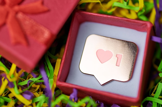 Come simbolo in confezione regalo rossa. come il pulsante del cuore del segno, il simbolo con il cuore e una cifra. marketing di rete sui social media. fondo multicolore della canutiglia.