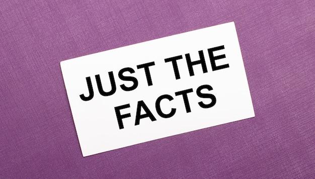 Su uno sfondo lilla, un cartoncino bianco con la scritta just the facts