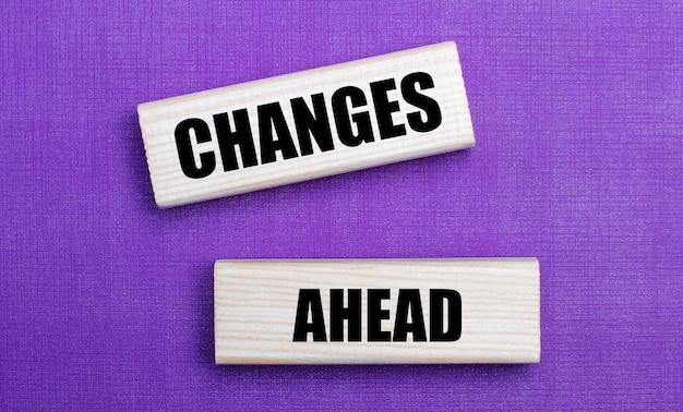Su uno sfondo lilla luminoso, blocchi di legno chiaro con il testo cambiamenti in avanti