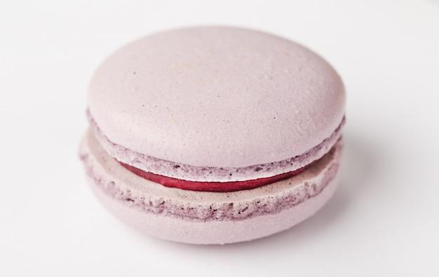 Maccheroni lilla dei biscotti su un fondo bianco di colore marrone con il materiale da otturazione, isolato.