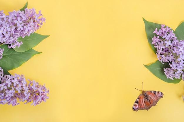 Fiori lilla e una farfalla su una parete gialla con spazio di copia