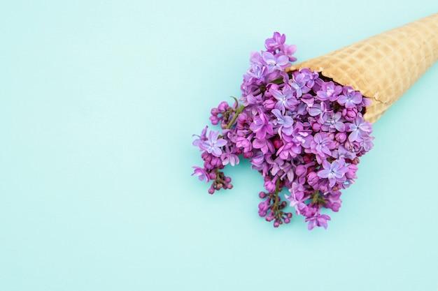 Fiori lilla in un cono gelato su sfondo blu.